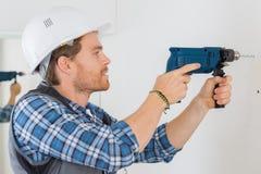 Сверля отверстие на стене стоковое изображение rf