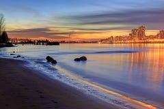 Света зарева и города захода солнца отражая над речной водой и пляжем Стоковая Фотография RF