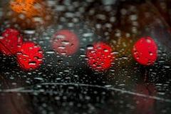 Света ночи городского движения увиденные через лобовое стекло в ненастной погоде абстрактная предпосылка Концепция города ночи Стоковая Фотография