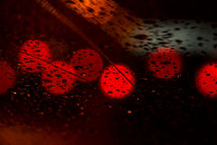 Света ночи городского движения увиденные через лобовое стекло в ненастной погоде Абстрактная предпосылка городского города в ноче Стоковое Фото