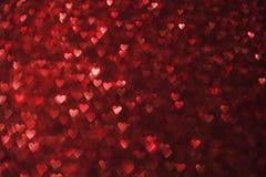 Света предпосылка сердец, Sparkles красного цвета формы сердца Стоковые Фотографии RF