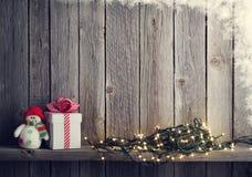 Света рождества, игрушка снеговика и подарочная коробка Стоковое фото RF