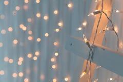 Света рождества горя на белой деревянной предпосылке Задняя часть Нового Года Стоковое Фото