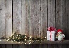 Света рождества, игрушка снеговика и подарочная коробка Стоковая Фотография