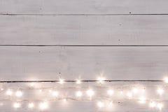 Света рождества на белизне покрасили деревянную предпосылку с sp экземпляра стоковые фотографии rf