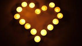 Света чая формы сердца горящие Свечи чая светлые формируя форму сердца Концепция темы влюбленности сток-видео