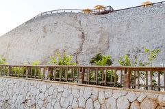 Светлая высокая каменная стена с деревянными рельсами и отвесный утес на фоне зонтиков от солнца и голубого неба в тропике Стоковое Изображение