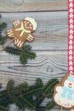 Светлая деревянная затрапезная предпосылка с печеньями пряника и елевыми ветвями Стоковая Фотография