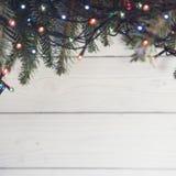 Светлая деревянная предпосылка рождества или Нового Года с ветвями ели и fairy светами Стоковые Фотографии RF