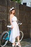 Светлая женщина полагается на ретро велосипеде против темной стены стоковое изображение