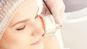 Светлая ультракрасная терапия Процедура по головы косметологии Сторона женщины красоты Косметический прибор салона Лицевое подмол стоковые изображения