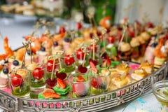 Светлые закуски, canap s с шпиком, сыром, мясом, соусом, томатами вишни Закуски для партий стоковая фотография