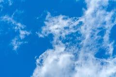 Светлые пушистые облака против яркой предпосылки голубого неба стоковое фото rf