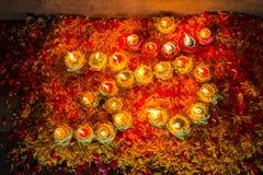светлые свеча и flower& x27; s украшает OM символ индусского reli стоковая фотография
