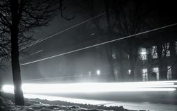 Светлые следы проходить автомобили вечером Туман на улицах города ночи стоковые фото