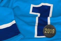 Светлый - голубые свитер и шайба хоккея стоковые фото