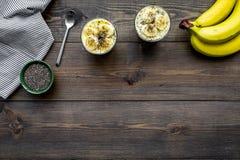 Светлый десерт плодоовощ для уменьшения Пудинг банана с семенами chia superfood на темной деревянной предпосылке с синью Стоковая Фотография