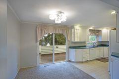 Светлый домашний интерьер с белым cabinetry кухни стоковое изображение