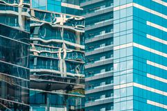 Светлый отражать в стеклянных окнах современных высокорослых больших административных зданий создавая интересные современные абст стоковое изображение rf