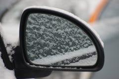 Светлый снег на зеркале серебряного автомобиля, отраженном в зеркале Первый чистый пушистый снег стоковые фото