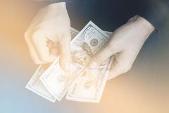 Светлый тонизировать белого молодого человека подсчитывает деньги, 100 новых bil доллара Стоковые Фотографии RF