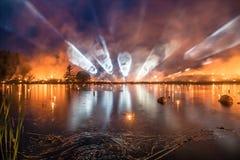 Световые лучи над озером пока лес и трава горят дальше назад Стоковое Изображение