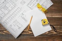 Светокопии, карандаш, защитные стекла, стальная лента, карандаш и белая бумага лежа на предпосылке деревянного стола Стоковые Фото