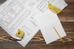 Светокопии, карандаш, защитные стекла, стальная лента, карандаш и белая бумага лежа на предпосылке деревянного стола Стоковые Фотографии RF