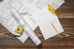 Светокопии, карандаш, защитные стекла, стальная лента, карандаш и белая бумага лежа на предпосылке деревянного стола Стоковая Фотография