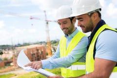 Светокопия инженера и работника наблюдая на строительной площадке Стоковое Изображение