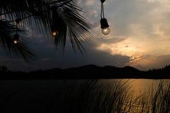 Светлая и темнота, пейзаж силуэта захода солнца с электрическими лампочками Стоковая Фотография