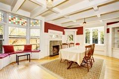 Светлая столовая в красных стенах и белых деревянных утесках Стоковые Изображения