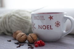 Светлая чашка с снежинками и Noel на переднем плане Стоковое Изображение
