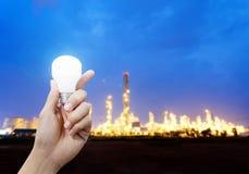 Светлая энергия для индустрии, руки держа электрическую лампочку в промышленной теме Стоковая Фотография