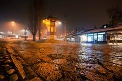Свет вокруг квадрата с Sebilj - фонтана Bascarsija ночи стиля псевдо-тахты деревянного Стоковые Изображения RF