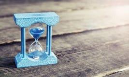 Свет - голубые часы на деревянной предпосылке, винтажном тоне цвета стоковые фото