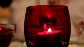 Свет горящей свечи внутри красного стекла акции видеоматериалы