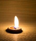 Свет горящей свечи на циновке Стоковые Изображения