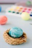 Свет - голубое пасхальное яйцо цвета на гнезде над яркой предпосылкой Стоковые Фото