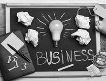 свет идеи дела шарика кредиток сверх Белая лампа с бумагой, тетрадью, ручкой, мелом, копилкой, номерами и резинками Доска с канце Стоковое фото RF