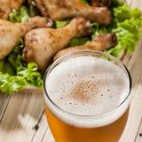 Светлое пиво и испеченные ноги цыпленка Стоковое Фото
