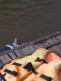 Светлооранжевый спасательный жилет на старом деревянном сплотке на Kw реки Стоковая Фотография RF
