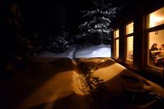 Свет печной трубы коттеджа освещает снег снаружи на зиме Стоковое фото RF