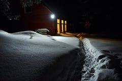 Свет печной трубы коттеджа освещает снег снаружи на зиме Стоковая Фотография RF