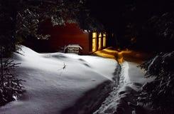 Свет печной трубы коттеджа освещает снег снаружи на зиме Стоковые Фотографии RF