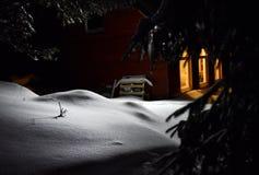 Свет печной трубы коттеджа освещает снег снаружи на зиме Стоковое Изображение RF
