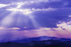 Свет Солнця через небо облака над горой стоковое изображение