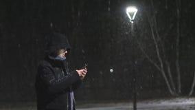 Свет человека на улице Парень смотрит в его smartphone Оно ` s идя снег на фоне лампы движение медленное видеоматериал