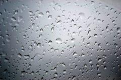 Свет через стекло с дождевыми каплями Стоковое Изображение RF