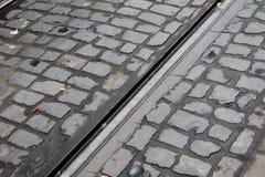 Светлые следы поезда рельса в улице булыжника стоковая фотография rf